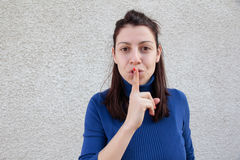 Young woman making silence sign. Young woman making silent sign with finger on mouth  in front of grey wall Stock Images