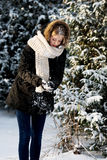 Young woman making snowball. Teenage woman making snowball to fight Stock Photo