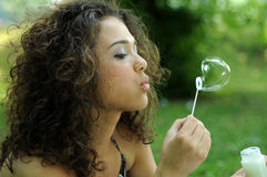 Young woman making soap bubbles Stock Images