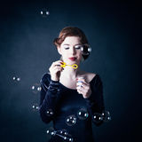 Young woman making soap bubbles Royalty Free Stock Photography