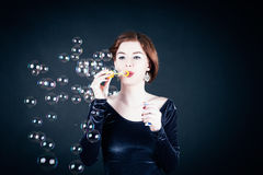Young woman making soap bubbles Royalty Free Stock Photo