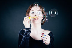 Young woman making soap bubbles royalty free stock image