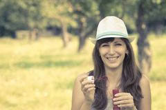 Young woman making soap bubbles in summer park. Stock Image