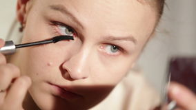 Young woman is making up her eyes. Stock Photo