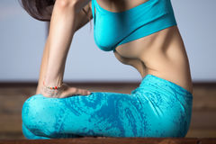 Young woman making Upward Abdominal Lock, studio evening practic Stock Photo