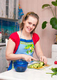 Young woman making vegetarian vegetable salad. Beautiful young woman making vegetarian vegetable salad Royalty Free Stock Images