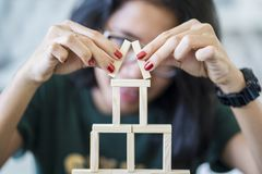 Young woman making a wooden blocks house stock image