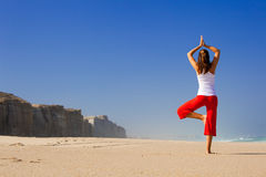 Young woman doing Yoga on beach Stock Photography