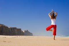 Young woman doing Yoga on beach Stock Photography