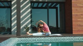 Young woman making yoga exercise near pool. Business woman make yoga after work stock video