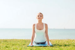 Young woman making yoga exercises outdoors Stock Images