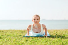 Young woman making yoga exercises outdoors Royalty Free Stock Photography