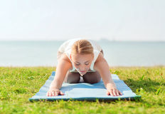 Young woman making yoga exercises outdoors Royalty Free Stock Images