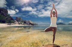 Young woman making yoga tree pose over beach Royalty Free Stock Photo