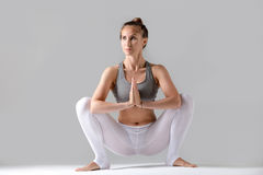 Young woman in Malasana pose, grey studio background. Young attractive woman practicing yoga, sitting in Garland exercise, Malasana pose, working out wearing Royalty Free Stock Photography