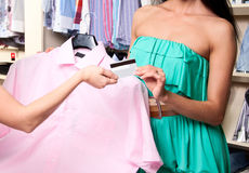Young woman in mall buying clothes. Payment of purchase by a plastic card Stock Photos