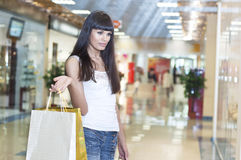 Young woman in mall buying clothes. Payment of purchase by a plastic card Stock Images