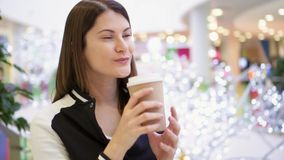 Young woman in mall drinking coffee from brown paper cup. White Christmas decorations on background stock video footage