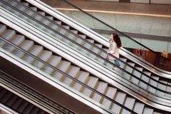 Young woman at the Mall rise up by escalator, view from the top. Young woman at the Mall going down the escalator, view from top Royalty Free Stock Photo