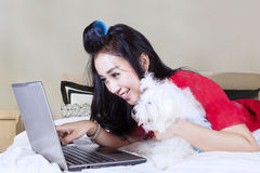 Young woman with Maltese dog and laptop. Portrait of beautiful woman pointing at the screen laptop while lying on the bed with Maltese puppy in the bedroom Royalty Free Stock Image