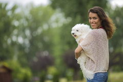 Young woman with a maltese dog. Outdoors Royalty Free Stock Photo