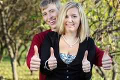 Young woman and man behind her smile and thumb up in park Royalty Free Stock Photography