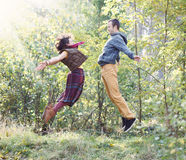 Young woman and man in bright clothes jumping to meet each other. Young women and men in bright clothes jumping to meet each other in the park Royalty Free Stock Photo