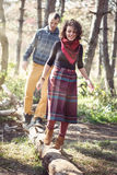 Young woman and man in bright clothes walking along fallen trunk Stock Images