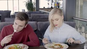 Young woman and man are at business lunch in restaurant. American people eat sitting at table in cafe indoors. Beautiful couple enjoys delicious meal, using stock video