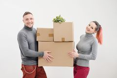 A young woman and a man carry heavy cardboard boxes with things. White light apartment. They laugh and kiss. stock image