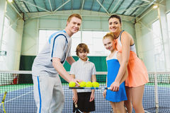 Young woman and man or coach teaching children how to play tennis on a court indoor Royalty Free Stock Photography