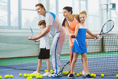 Young woman and man or coach teaching children how to play tennis on a court indoor Stock Photo