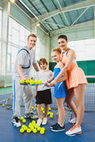 Young woman and man or coach teaching children how to play tennis on a court indoor Royalty Free Stock Photos