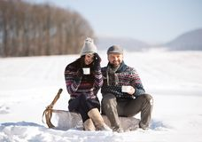 Young woman and man with cup of coffee in winter nature. Stock Photos