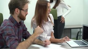 Young woman and man discuss a project on a computer and they call their colleague to comment and help. Creative business. Man and young woman discuss a project stock footage