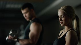Young woman and man doing a fitness workout with dumbbells. Athletic young woman and man doing a fitness workout with dumbbells on black studio background stock video footage