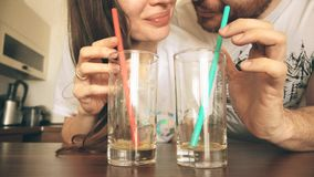 Young woman and man drinking juice with straws together. Healthy lifestyle or funny competition concepts Royalty Free Stock Photos