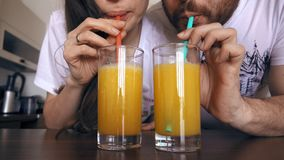 Young woman and man drinking orange juice with straws together. Healthy lifestyle or funny competition concepts. Young women and men drinking orange juice with Royalty Free Stock Images