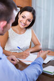 Young woman and man with financial documents in agency Royalty Free Stock Photos