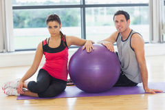 Young woman and man with fitness ball sitting at gym Royalty Free Stock Image