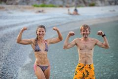 Young woman and man flexing their muscles jokingly Royalty Free Stock Photo
