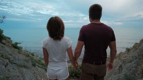 Young woman and man go to sea shore on summer evening outdoors. stock video footage