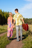 Young woman and man with guitar go on road Stock Image