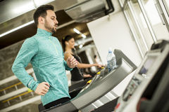 Young woman and man at the gym exercising and run on a treadmill Stock Image