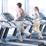 Young woman and man at the gym exercising. Running. Young woman and man at the gym exercising. Run on on a machine Royalty Free Stock Image