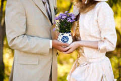 Young woman and man holding a bouquet of flowers. Young woman and man holding a bouquet of purple flowers Stock Photos