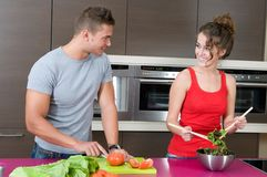 Young woman and man in the kitchen with salad. Young woman and man in their kitchen with salad Royalty Free Stock Photo