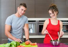 Young woman and man in the kitchen with salad. Young woman and man in their kitchen with salad Royalty Free Stock Photos