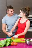 Young woman and man in the kitchen with salad. Young woman and man in their kitchen with salad Stock Photography