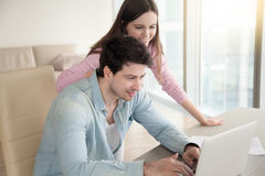 Young woman and man with laptop computer at home office. Handsome guy and pretty women sitting and talking indoors, using computer laptop. Working online Royalty Free Stock Image